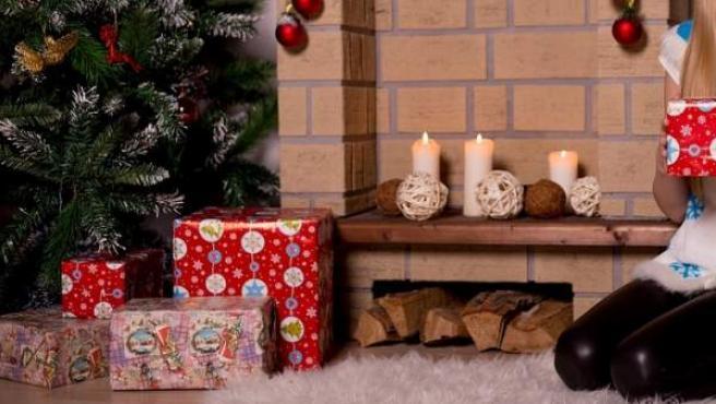 Una niña posa junto a los regalos de Navidad.