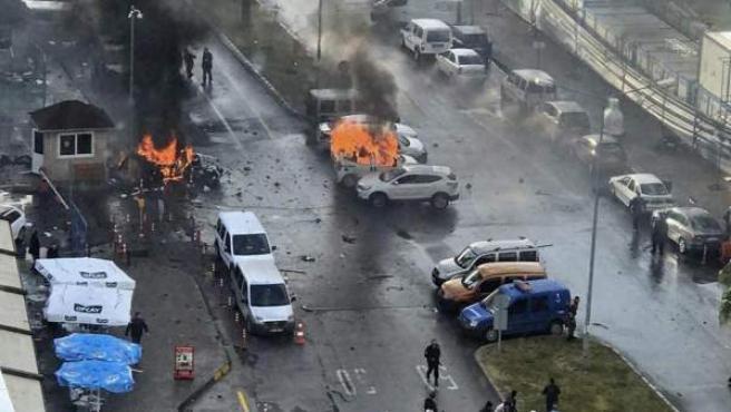 Imagen de varios vehículos envueltos en llamas mientras agentes de policía asisten a los heridos después de que explotara un coche bomba frente al Palacio de Justicia de Esmirna, en el oeste de Turquía.