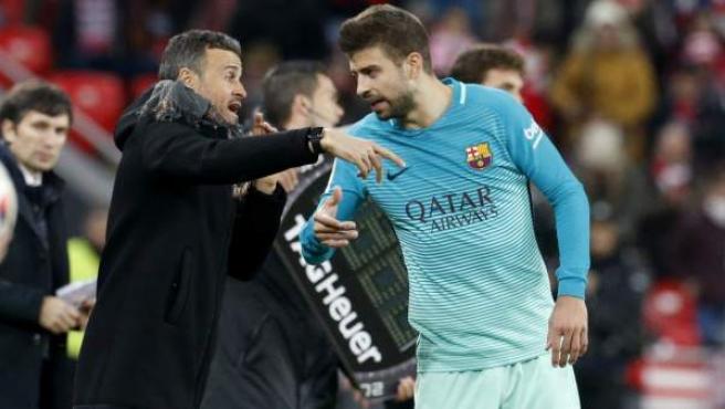El defensa del F.C Barcelona, Gerard Piqué (d), recibe indicaciones del técnico del equipo barcelonista, Luis Enrique, durante el encuentro correspondiente a la ida de los octavos de final de la Copa del Rey, que han disputado este jueves frente al Athletic de Bilbao en el estadio de San Mamés, en la capital vicaína.