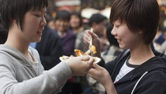 Dos mujeres asiáticas comen en un restaurante.