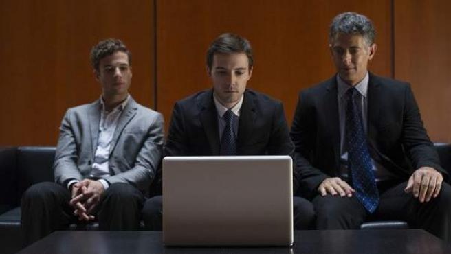 Tres hombres miran la pantalla de un ordenador portátil.