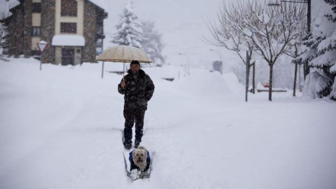 Un hombre camina junto a su perro por la localidad de Benasque, tras la gran nevada caída en el Pirineo.