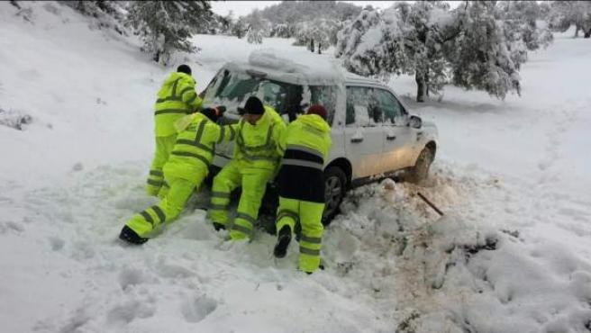 Los bomberos rescatan un coche atrapado por la nieve.