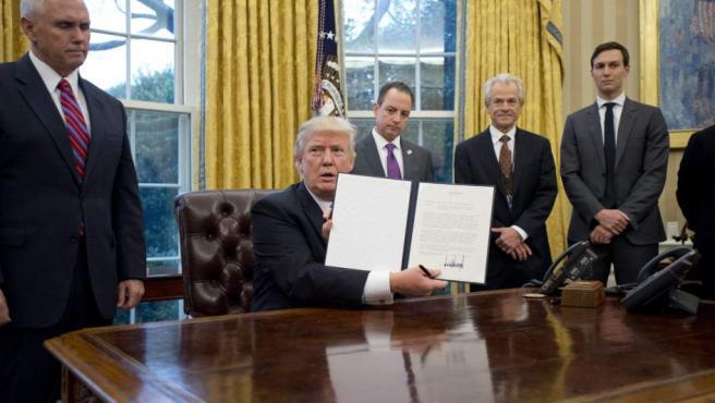 El presidente estadounidense, Donald Trump (c), muestra el pasado mes de enero la orden ejecutiva para sacar a EE UU del acuerdo comercial TPP (Acuerdo de Asociación Transpacífico), en el Despacho Oval de la Casa Blanca.