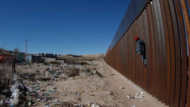 Un hombre intenta escalar la reja fronteriza en Ciudad Juárez, México, en el límite con los estados norteamericanos de Texas y Nuevo México.
