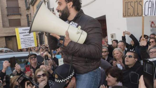 El doctor Candel se dirige a los ciudadanos a hombros de un agente de Policía.