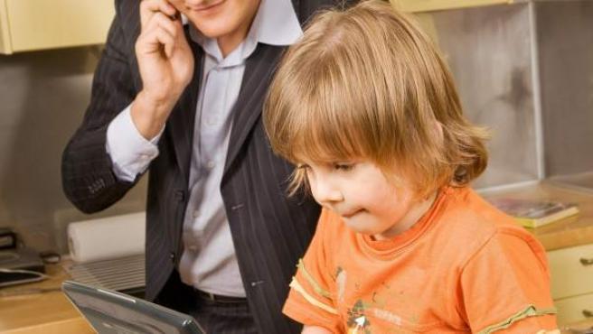 Un niño usa un portátil en presencia de su padre.