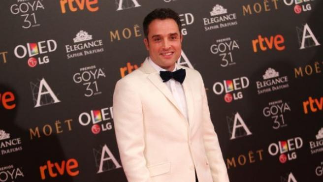 El actor y director Daniel Guzmán, con esmoquin blanco y pajarita negra, se para ante los fotógrafos en la alfombra roja de los Goya 2017.