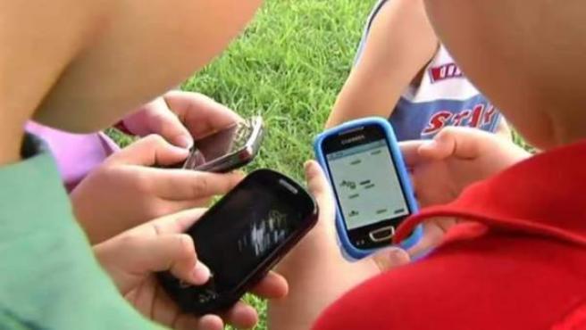 Varios niños usando sus teléfonos móviles.
