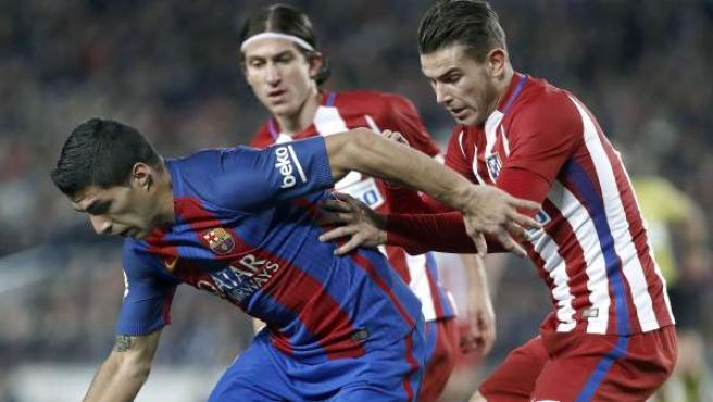 El defensa del Atlético de Madrid Lucas Hernández (d) presiona al uruguayo Luis Suárez (i), del FC Barcelona.