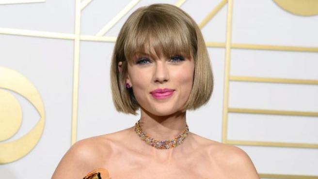 La cantante Taylor Swift sostiene sus premios Grammy a mejor video musical por Bad Blood, Mejor álbum de pop vocal y mejor álbum del año por su trabajo 1989, durante la ceremonia de entrega de estos galardones en el Staples Center en Los Ángeles (EE UU)