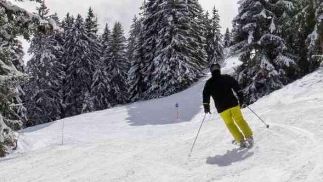 Un esquiador disfruta de la nieve y el sol en los Alpes.