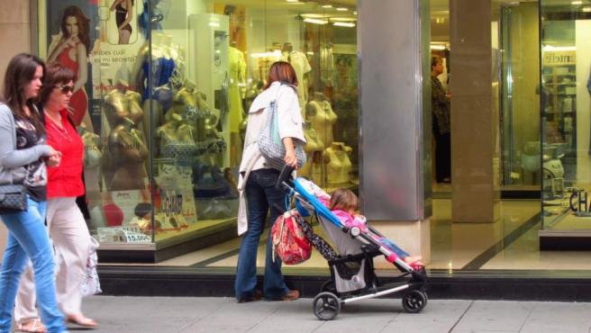 Una mujer mira un escaparate mientras sujeta el carrito de un bebé.