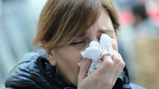 Mujer con gripe sonándose.