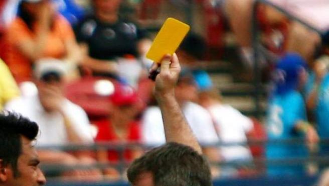 Un árbitro señala una tarjeta amarilla.