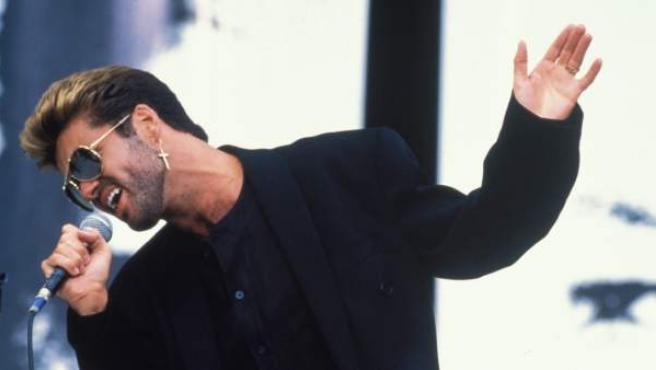 El cantante George Michael con la que fue su imagen más popular: pendiente de oro en forma de cruz, gafas con montura dorada, mechas y completamente vestido de negro.