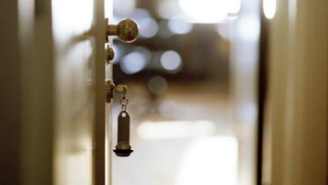 Llaves colocadas en la cerradura de una puerta abierta.