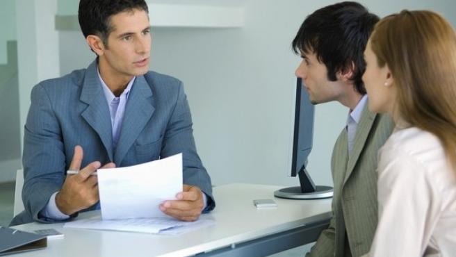 Un comercial asesora a unos clientes.