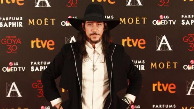El actor Óscar Jaenada llamó la atención en el photocall de los Goya 2016 por su curioso estilismo con sombrero de ala ancha, abrigo negro y botines altos.