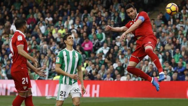 El centrocampista del Sevilla Vicente Iborra (d) remata un balón ante el defensa francés del Betis Aissa Mandi (c).