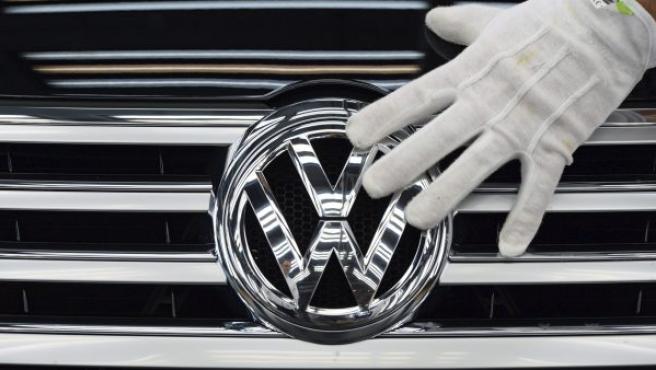 La mano de un empleado mientras toca el logotipo de Volkswagen en la planta de la compañía en Dresde (Alemania).