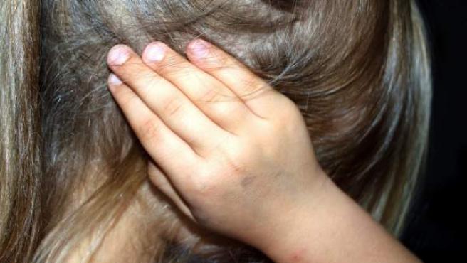 Una niña, tapándose los oídos.