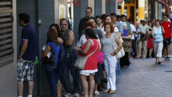 Un grupo de personas hacen cola para entrar en un oficina de empleo de Madrid.
