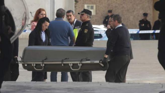 Operarios trasladan el féretro con los restos de un joven que ha muerto en un tiroteo en la zona norte de Granada.