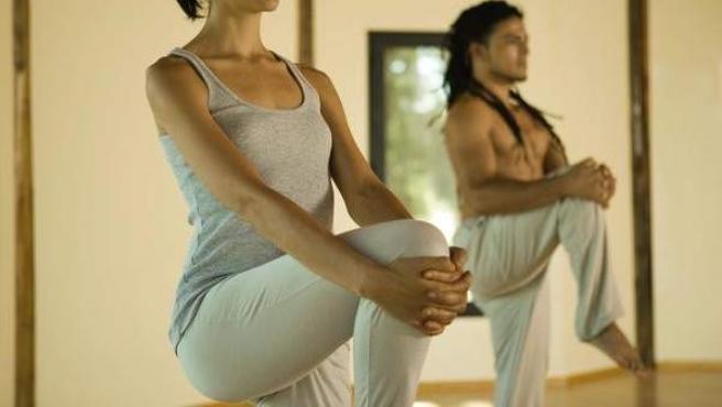 Dos personas realizan una postura de yoga con una sola pierna en el suelo.