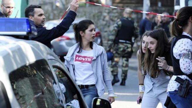 Agentes de policía galos permiten a varias jóvenes abandonar el lugar de un tiroteo en un instituto de Grasse.
