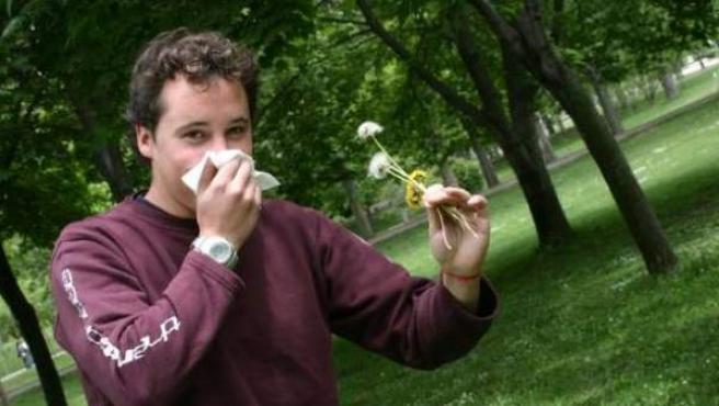 Un joven alérgico, sosteniendo unas plantas en plena floración.