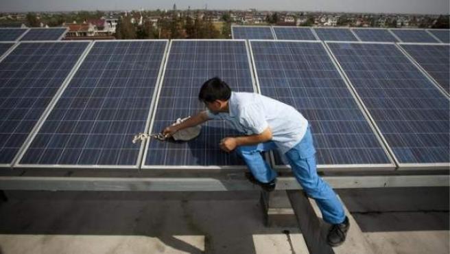 Un trabajador limpia una placa solar en la azotea de un edificio.