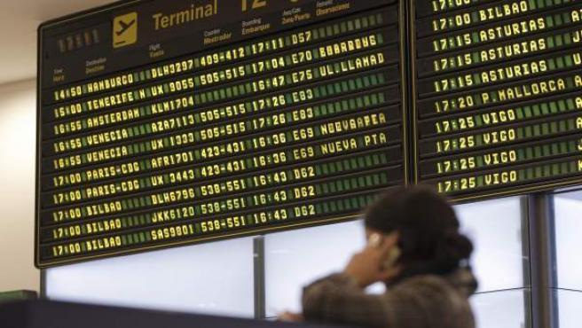 Una mujer contempla los paneles informativos con la actividad de los vuelos del aeropuerto de Barajas.