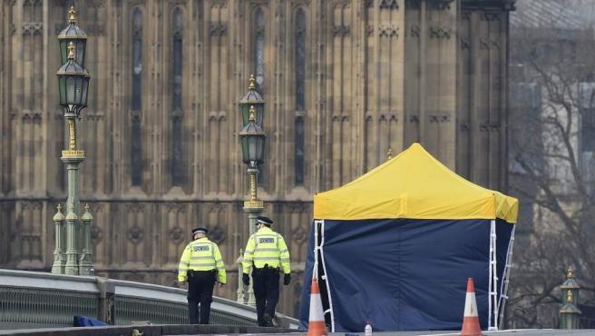 Varios miembros de la policía forense inspeccionan los alrededores del puente de Westminster.