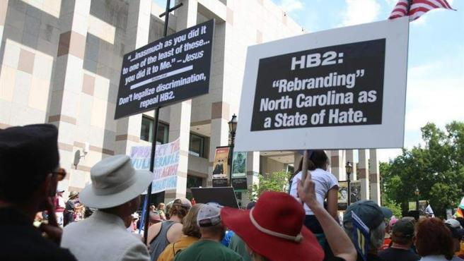 Varias personas sostienen carteles en contra de la ley HB2 durante una protesta del movimiento 'Lunes Moral' el 25 de abril 2016, frente al edificio de la Asamblea Legislativa de Carolina del Norte.