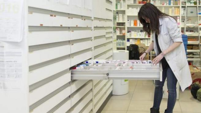 Una farmacéutica buscando un medicamento.