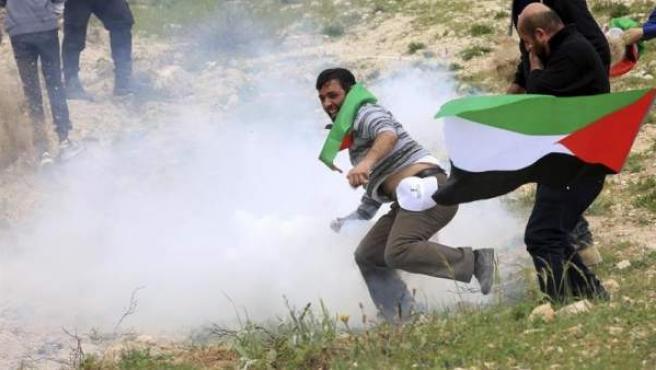 Un palestino devuelve a la policía israelí una granada lacrimógena durante una manifestación para rememorar el Día de la Tierra, en el asentamiento de Kiryat Arba, en la ciudad cisjordana de Hebrón, Palestina.