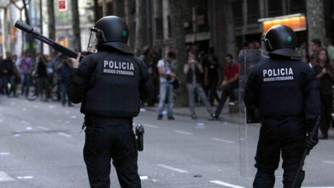 Dos antidisturbios de los Mossos d'Esquadra, uno de ellos portando una escopeta de balas de goma.