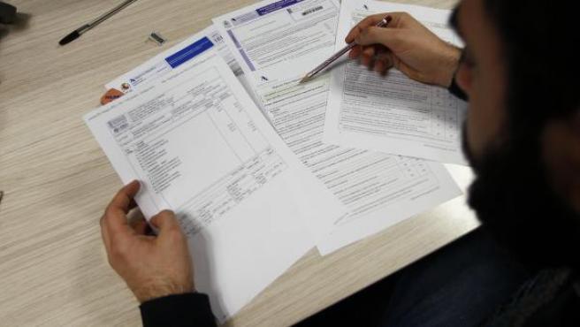 Un joven completa el formulario de la declaración de la renta.