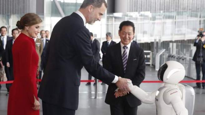 El rey Felipe de España (c) y la reina Letizia (i) saludan el robot Asimo de Honda, durante una visita al Museo de la Ciencia Emergente y la Innovación (Miraikan), en Tokio (Japón).