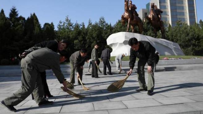 """Trabajadores norcoreanos limpian el suelo frente a una estatua del fundador de su país, Kim Il-sung, y el """"querido líder"""" Kim Jong-il en Pyongyang."""