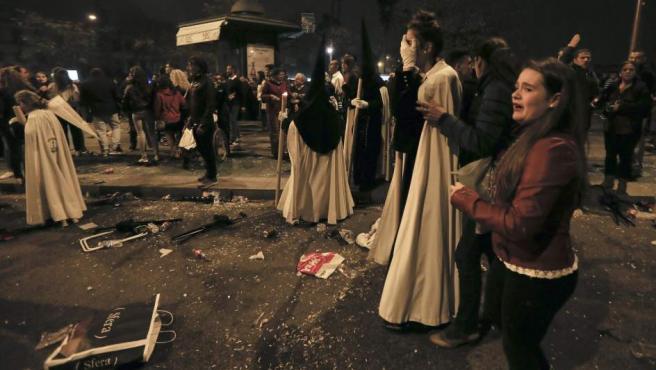 Los nazarenos y los feligreses intentan recomponerse tras las estampidas de la Madrugá en Sevilla.