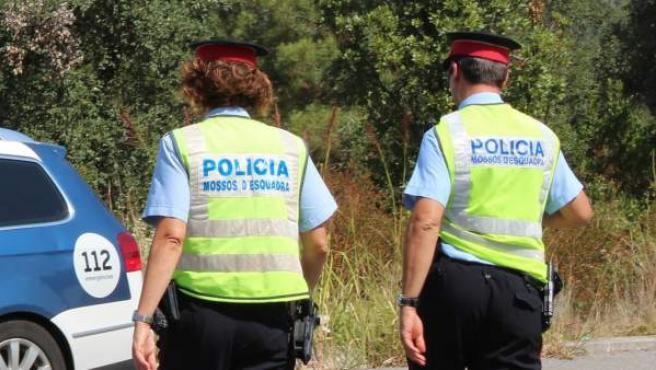 Imagen de dos Mossos d'Esquadra dirigiéndose a su coche patrulla.
