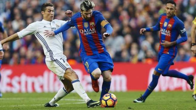 Cristiano Ronaldo trata de robarle un balón a Leo Messi.