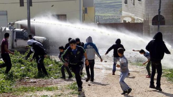 Niños palestinos huyen de los cañones de agua del ejército israelí durante una protesta contra los asentamientos judíos en Qadomen, en la localidad de Kofr Qadom, cerca de Nablus, Cisjordania.