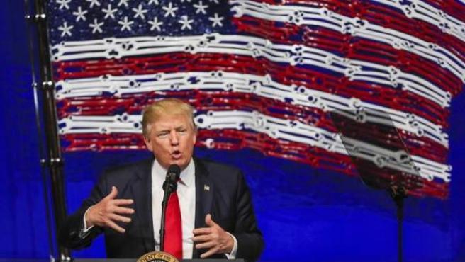 """El presidente de los Estados Unidos, Donald Trump, delante de una bandera estadounidense hecha con herramientas en la sede de Snap-on Tools, en Kenosha (EE.UU), donde habló sobre su plan """"Compra Americano - Contrata Americano""""."""