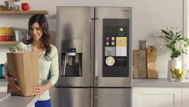 Una chica se dispone a guardar su compra en un frigorífico 'smart'.