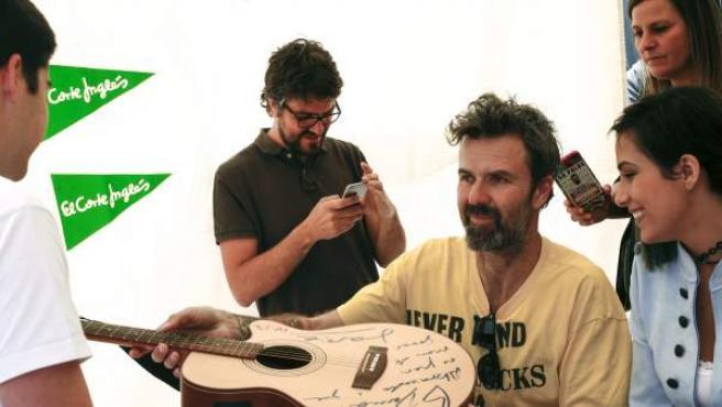 El cantante Pau Donés firma una guitarra en las Ramblas de Barcelona, durante la tradicional fiesta de Sant Jordi.