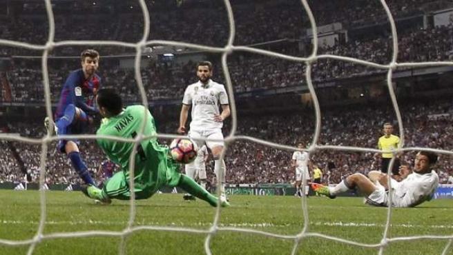 El guardameta costarricense del Real Madrid, Keylor Navas, consigue parar el disparo del defensa del FC Barcelona Gerard Piqué, durante el encuentro correspondiente a la jornada 33 de primera división, disputado en el Santiago Bernabéu.