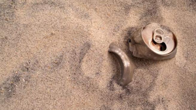 Una lata de refresco enterrada en baja la arena de una playa.